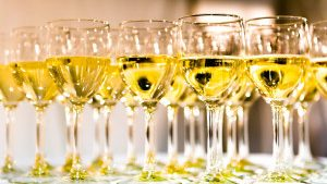 white wine glasses on white table thumbnail