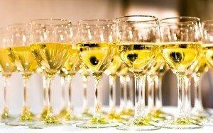 white wine glasses on white table thumbnail