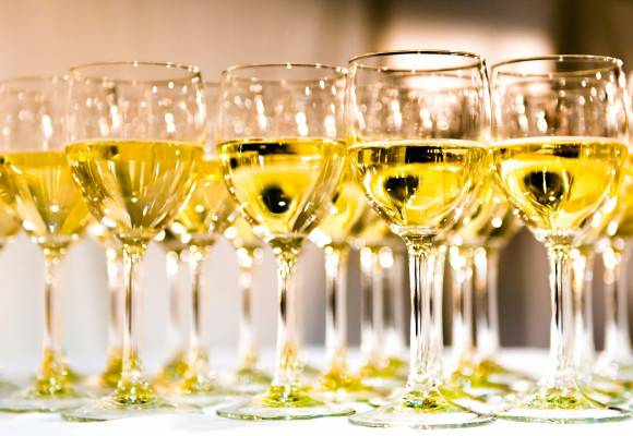 Glasses of white wine on a white table