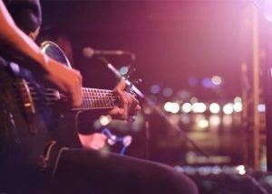 Live guitar performance on stage with glare