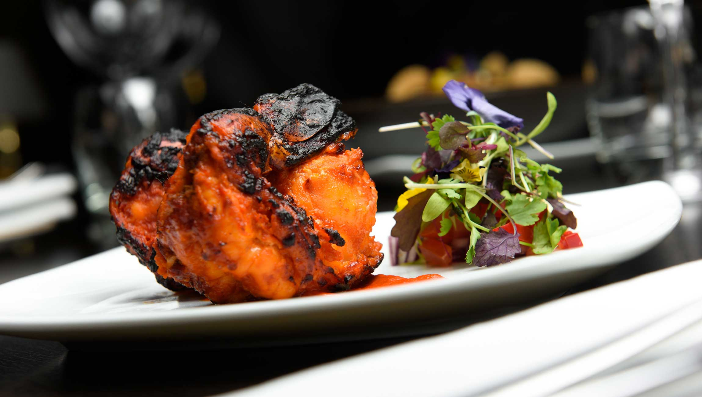 Indian cuisine dish on table with small salad garnish